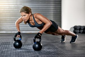 woman wearing gym clothes and doing press ups while holding kettlebells