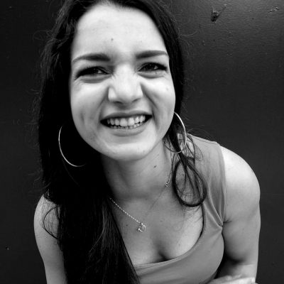 Victoria - 1-2-1 and online personal trainer. Black and white photo of a woman with long dark hair looking at the camera and smiling